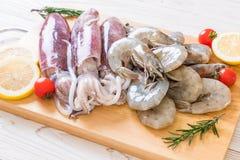 свежие морепродукты сырцовые (креветки, кальмары) на деревянной доске стоковое фото