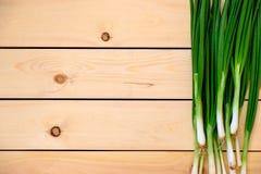 Свежие молодые зеленые луки на деревянном столе Стоковое Изображение