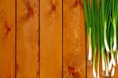 Свежие молодые зеленые луки на деревянном столе Стоковое фото RF