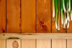 Свежие молодые зеленые луки на деревянном столе Стоковые Фотографии RF