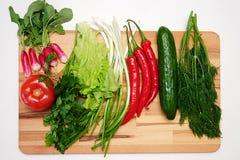 Свежие овощи и травы клали вне на деревянную доску стоковое фото rf