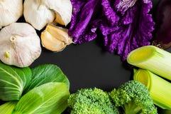Свежие овощи: капуста bok choy китайская, чеснок, брокколи, лук-порей и салат на черной предпосылке с космосом экземпляра еда здо стоковая фотография