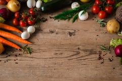 Свежие овощи на деревянной таблице предпосылки Картошки, морковь, корень петрушки, цукини, свекла, лук, лук-порей и томаты Стоковое Изображение RF