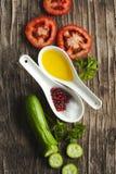 Свежие овощи, оливковое масло, травы и специи на деревянной предпосылке Стоковые Изображения