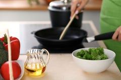 Свежие овощи, салат и постное масло на предпосылке женщины варят плитой в кухне Стоковые Изображения RF