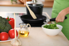 Свежие овощи, салат и постное масло на предпосылке женщины варят плитой в кухне Стоковое Изображение