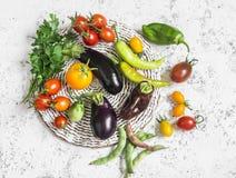 Свежие овощи - томаты, баклажаны, перцы, фасоли, петрушка на светлой предпосылке стоковая фотография