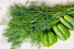 Свежие огурцы, зеленые перцы и укроп на деревянном столе стоковые изображения