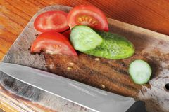 Свежие огурцы и томаты на разделочной доске Отрезанные овощи стоковая фотография