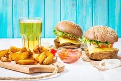 Свежие домодельные бургеры, зажаренные картошки и пиво служили на белой деревянной таблице Стоковое Фото