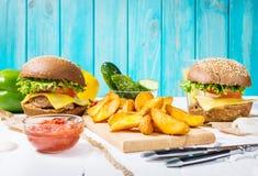 Свежие домодельные бургеры, зажаренные картошки и сок служили на белой деревянной таблице Стоковое фото RF