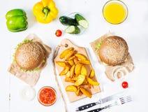 Свежие домодельные бургеры, зажаренные картошки и сок служили на белой деревянной таблице Стоковые Изображения