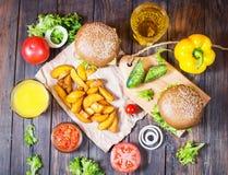 Свежие домодельные бургеры, зажаренные картошки, пиво и сок служили на деревянной таблице Стоковое фото RF