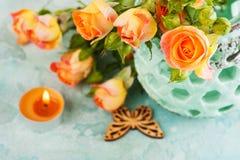 Свежие оранжевые розы цветут в вазе мяты и освещенной свече Стоковые Изображения RF