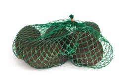 Свежие органические авокадоы в зеленой сумке строки на белой изолированной предпосылке, здоровая концепция hass еды, космос экзем стоковые фотографии rf