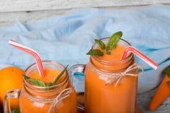 Свежие, органические апельсин и сок моркови Опарникы вполне встряхивания плодоовощ на свете - голубой предпосылки Пить и диеты вы Стоковое Изображение
