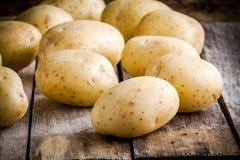 Свежие органические сырцовые картошки на старой таблице Стоковые Фото