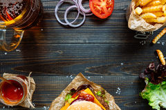 Свежие очень вкусные бургеры с французскими фраями, соусом и пивом на взгляд сверху деревянного стола Стоковое Изображение
