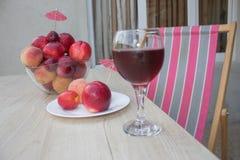 Свежие персики, нектарин и сливы на кухонном столе стеклянное красное вино Стоковое Изображение RF