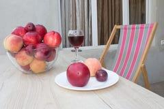 Свежие персики, нектарин и сливы на кухонном столе стеклянное красное вино Стоковые Фото