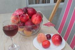 Свежие персики, нектарин и сливы на кухонном столе стеклянное красное вино Стоковые Изображения RF