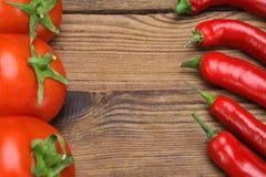 Свежие перцы и томаты на деревянной доске Стоковые Изображения