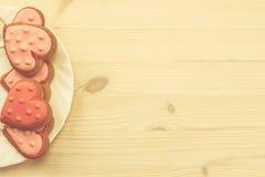 Свежие печенья на белой плите в форме сердца на деревянной предпосылке Стоковые Изображения