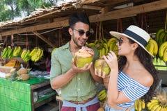 Свежие продукты уличного рынка плодоовощей азиата кокоса питья пар покупая, молодой человек и каникулы туристов женщины экзотичес Стоковое фото RF