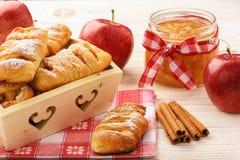 Свежие плюшки дрожжей с вареньем и циннамоном яблока на белой деревянной предпосылке Стоковое Фото