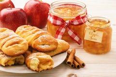 Свежие плюшки дрожжей с вареньем и циннамоном яблока на белой деревянной предпосылке Стоковое фото RF