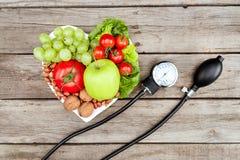 Свежие различные овощи, плодоовощи и датчик кровяного давления на деревянной поверхности, здоровой концепции еды Стоковые Изображения RF