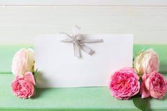 Свежие розовые розы и пустая бирка на зеленом деревянном agai предпосылки Стоковое Изображение