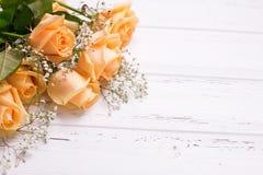Свежие розы цвета персика цветут на белой деревянной предпосылке Стоковое фото RF