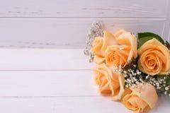 Свежие розы цвета персика цветут на белой деревянной предпосылке Стоковые Изображения