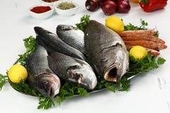 Свежие рыбы и овощ на плите Стоковые Изображения
