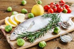 Свежие рыбы с овощами на деревянной доске Стоковые Изображения