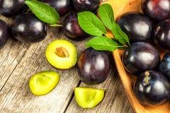 Свежие сливы на деревянном столе Продажи сбора плодоовощ свежих фруктов Стоковая Фотография RF
