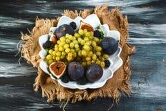 Свежие смоквы и виноградины на плите, черный деревянный стол Скопируйте текст Плоское положение стоковые изображения