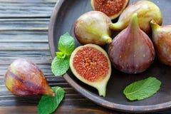 Свежие смоквы и листья мяты на деревянном диске Стоковые Изображения RF