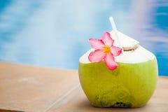 Свежие сок и орхидея коктеиля кокоса цветут на бассейне Стоковые Изображения
