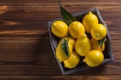 Свежие сочные желтые лимоны с листьями на деревянном столе стоковая фотография