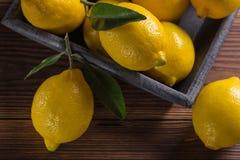 Свежие сочные желтые лимоны с листьями на деревянном столе стоковые фотографии rf
