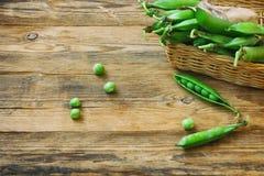 Свежие стручки сладостных зеленых горохов в корзине на таблице Стоковые Изображения