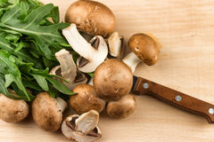 Свежие сырцовые грибы коричневеют грибы и зеленый arugula на woode Стоковое Изображение RF