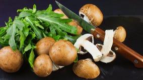 Свежие сырцовые грибы коричневеют champignons и зеленый arugula на dar Стоковые Фотографии RF