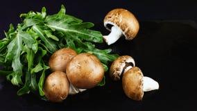 Свежие сырцовые грибы коричневеют champignons и зеленый arugula на dar Стоковые Изображения