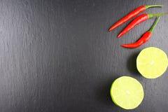 Свежие тайские перцы и известка chili на шифере покрывают текстуру предпосылки еды Стоковое Изображение