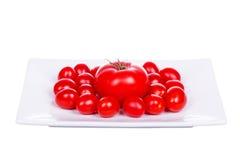 Свежие томаты вишни на плите изолированной на белизне Стоковое Изображение