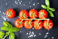 Свежие томаты вишни на черной предпосылке с специями верхняя часть соперничает Стоковые Фото