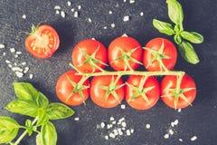 Свежие томаты вишни на черной предпосылке с специями верхняя часть соперничает Стоковое Изображение RF